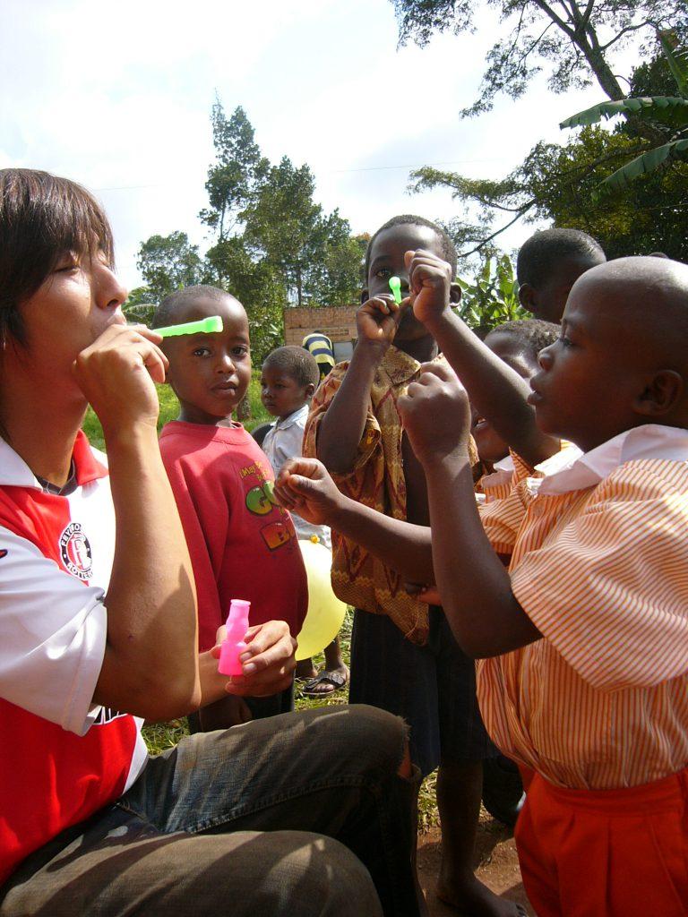 シャボン玉をするボランティアと子どもたち